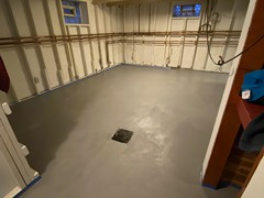 A resurface job we did in a basement. Filled in low spots and patched all repairs where needed using polymer cement. Finished with a polymer cement resurfacer that was tinted for a clean grey look.