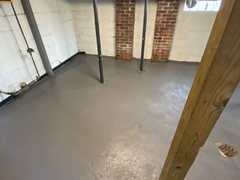 After repairs, the team resurfaced the entire basement floor using a skim coat to provide a neat, fresh finish and an extra layer of protection