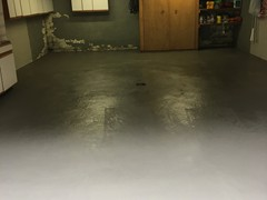 This garage floor needing power washing, crack repair, and resurfacing. The surface was finished with a skim coat of resurfacer.